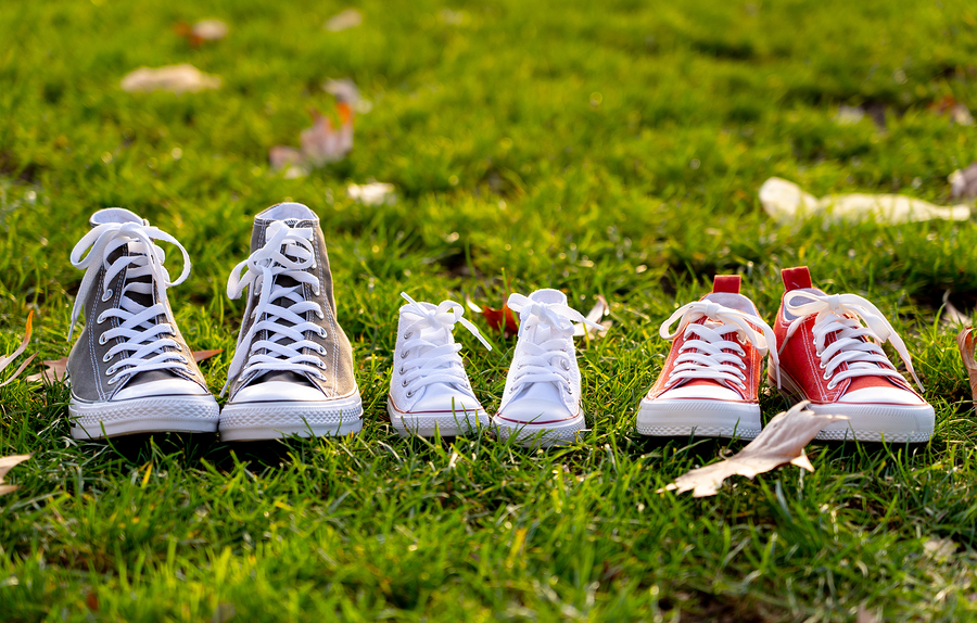 Conceptual image of family sneakers shoes in father mother and baby sizes on grass in beautiful autumn sunset light for togetherness Happy Family Expecting young parents and outdoors lifestyle.